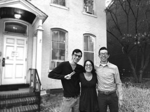 Portrait of three students smiling in front of building.